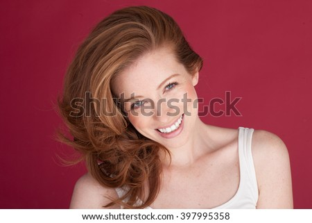 happy smiling woman with freckles on red with blue eyes  - stock photo