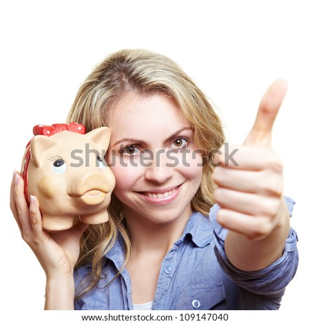 Happy smiling woman with piggy bank holding thumbs up - stock photo