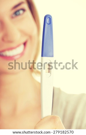 Happy smiling woman with pregnancy test - stock photo
