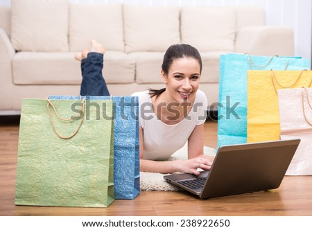 Happy, smiling woman with shopping bags is using laptop, looking at the camera and smiling. - stock photo