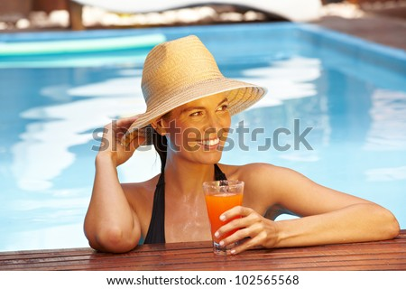 Happy smiling woman with straw hat in swimming pool - stock photo