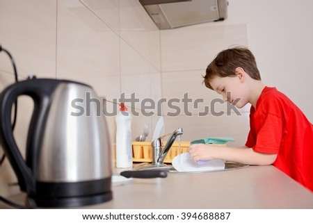 Happy, smiling 7 year old boy washes dishes in the kitchen. Dressed in a red t-shirt