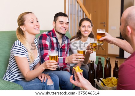 Happy smiling young adults drinking beer and laughing at home - stock photo