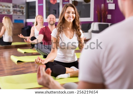 Happy smiling young adults having yoga class in sport club - stock photo