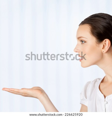 Happy smiling young beautiful business woman showing blank area for sign or copyspase, or some product, at office - stock photo