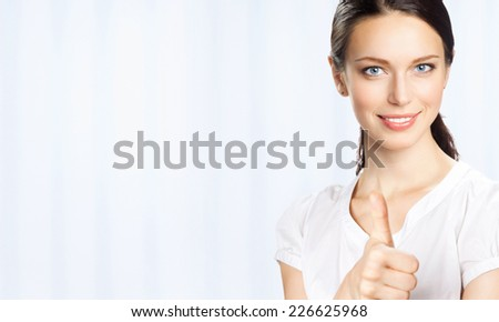 Happy smiling young beautiful business woman showing thumbs up gesture, at office, with blank area for sign or copyspase - stock photo