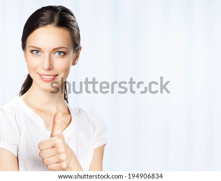 Happy smiling young beautiful business woman showing thumbs up gesture, at office, with copyspace - stock photo