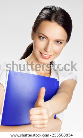 Happy smiling young beautiful business woman showing thumbs up gesture, on grey - stock photo