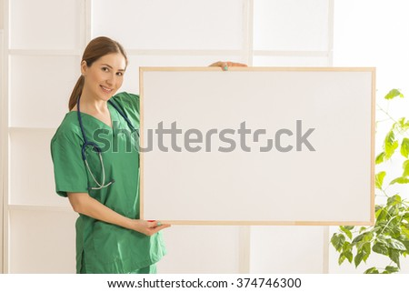 Happy smiling young beautiful female doctor showing blank area for sign or copy space. Nurse showing blank clipboard sign - medical concept - stock photo
