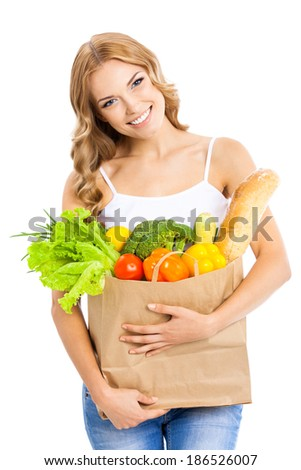 Happy smiling young beautiful woman holding grocery shopping bag with healthy vegetarian raw food, isolated over white background
