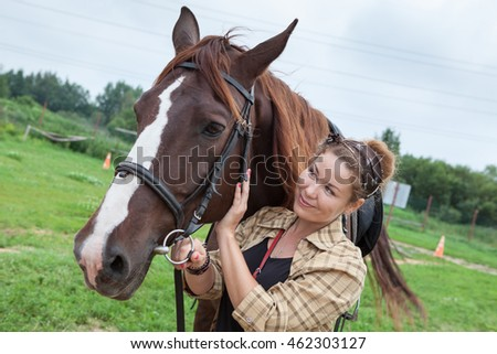 Happy smiling young beautiful woman is near a chestnut horse