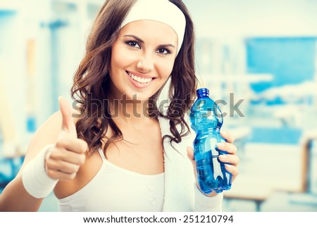 Happy smiling young beautiful woman showing thumbs up gesture, with bottle of water, at fitness club or gym - stock photo