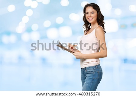 Happy smiling young beautiful woman with clipboard