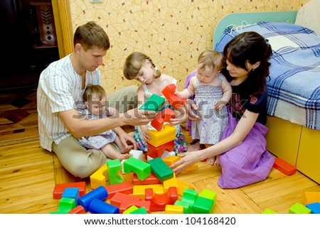 Happy smiling young big family - mother, father, elder daughter and two twins baby girls are building a house from toy cubes blocks on the floor. - stock photo