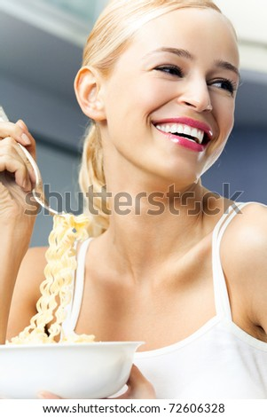 Happy smiling young blond woman eating spaghetti indoors - stock photo