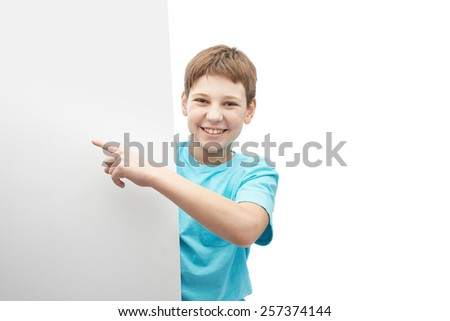 Happy smiling young boy in a cyan t-shirt, hiding behind an empty copyspace sheet of paper in front of him, composition isolated over the white background - stock photo