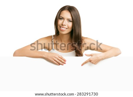 Happy smiling young brunette woman in tank top casual smart clothing, pointing on empty blank signboard with copyspace area for text or slogan, isolated over white background - stock photo