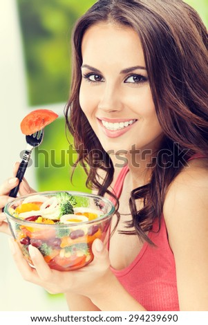 happy smiling young brunette woman with vegetarian vegetable salad, outdoors - stock photo