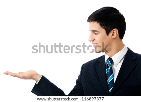 Happy smiling young business man showing blank area for sign or copyspase, isolated over white background