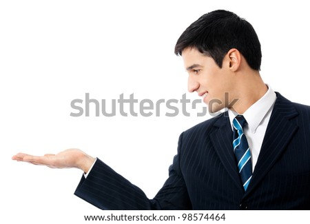 Happy smiling young business man showing blank area for sign or copyspase, isolated over white background - stock photo