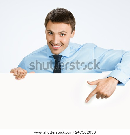 Happy smiling young business man showing blank signboard, over grey background, with copyspace area for text or slogan - stock photo