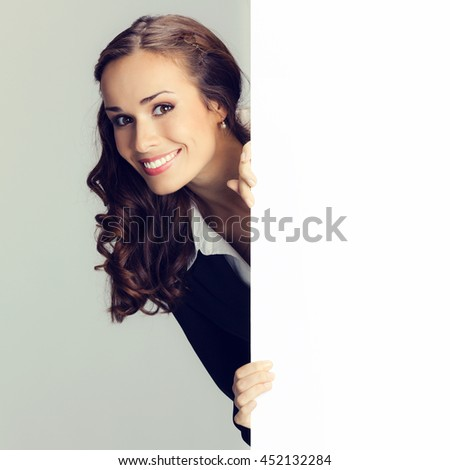 Happy smiling young business woman showing blank signboard - stock photo