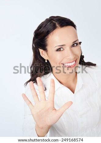 Happy smiling young business woman showing five fingers, against grey background