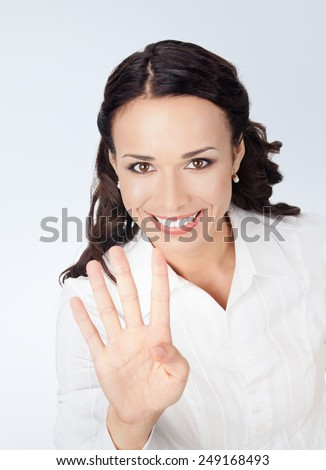 Happy smiling young business woman showing four fingers, against grey background