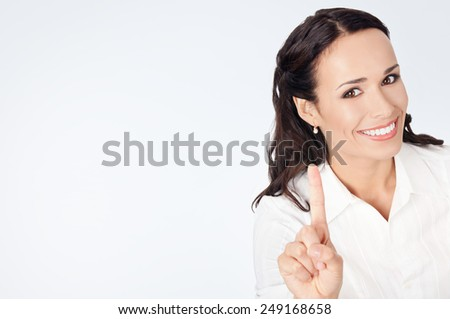 Happy smiling young business woman showing one finger, against grey background, with copyspace - stock photo