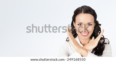 Happy smiling young business woman showing stop gesture, against grey background, with copyspace - stock photo