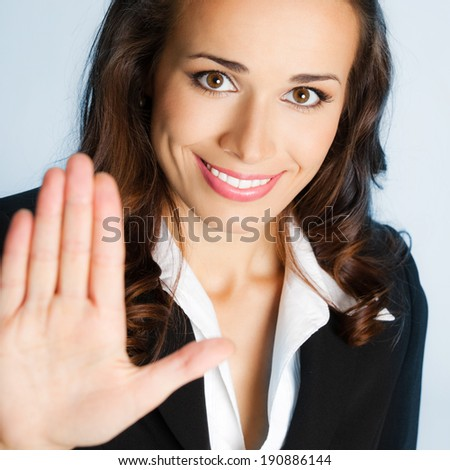Happy smiling young business woman showing stop gesture, over blue background - stock photo