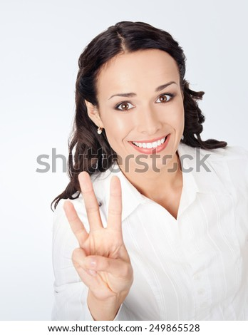Happy smiling young business woman showing three fingers, against grey background