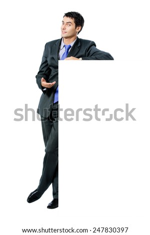 Happy smiling young businessman in blue tie, showing blank signboard with copyspace area for text or slogan, isolated against white background