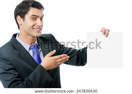 Happy smiling young businessman in blue tie, showing blank signboard with copyspace area for text or slogan, isolated against white background - stock photo