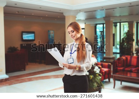 Happy smiling young businessman looking at the paper in the office - stock photo