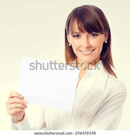 Happy smiling young businesswoman in white business style clothing showing blank signboard with copyspace area for slogan or text message - stock photo