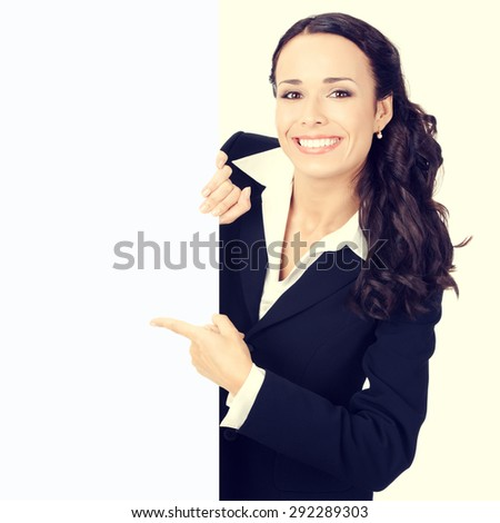 Happy smiling young businesswoman pointing on blank signboard