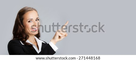 Happy smiling young businesswoman showing blank copyspace area for text or slogan - stock photo
