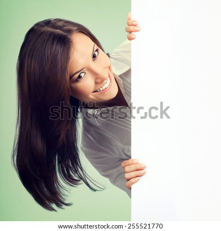 Happy smiling young businesswoman showing blank signboard with copyspace area for text or slogan, on green background - stock photo