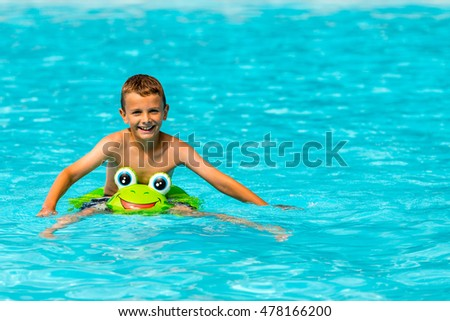 Happy smiling young caucasian boy in swimming pool at holiday resort on sunny summer day.
