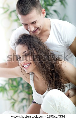 happy smiling young couple at home fooling around