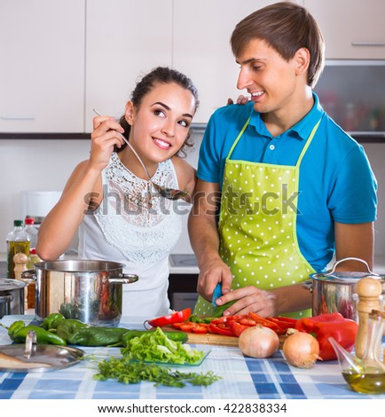 Happy smiling young couple preparing dinner with vegetables together at kitchen