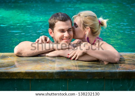 Happy smiling young couple relaxing in a swimming pool on a poolside in tropical resort - stock photo