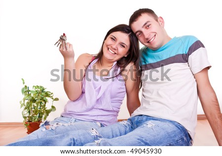 happy smiling young couple showing keys to new apartment - stock photo