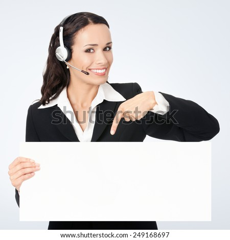 Happy smiling young customer support phone operator in headset showing blank signboard, against grey background, with copyspace