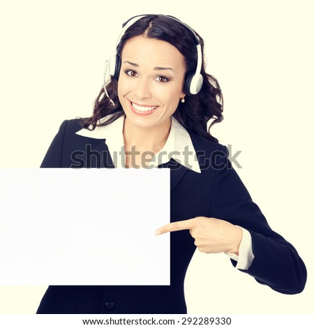 Happy smiling young customer support phone operator or businesswoman in headset pointing blank signboard - stock photo
