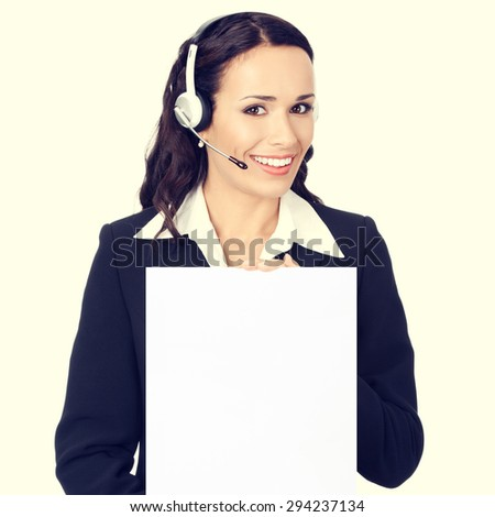 Happy smiling young customer support phone operator or businesswoman in headset showing blank signboard