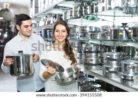 Happy  smiling young family choosing new pans in kitchenware section in supermarket . Focus on woman