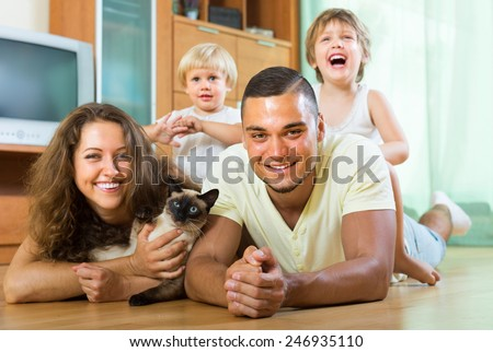 Happy smiling young family of four laying on the floor in living room with kitten. Focus on man - stock photo