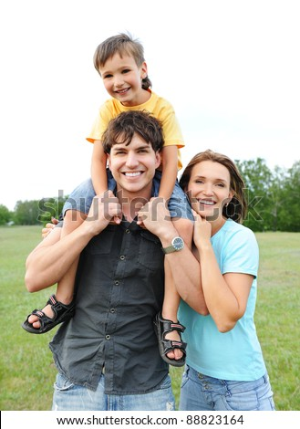 Happy smiling young family posing on nature. Three person - stock photo